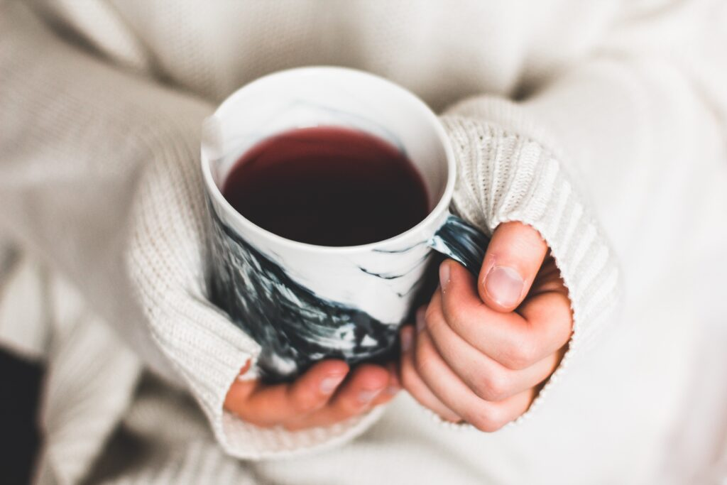 Hands in a sweater holding a warm mug of tea
