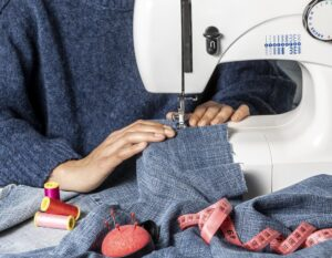 Hands sewing with machine, close up