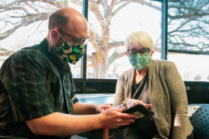 A masked man assists a masked woman with a tablet computer