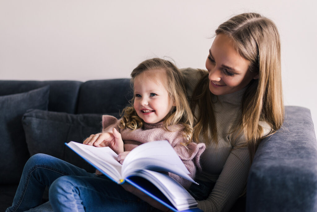 Happy mother and little daughter reading book, sitting on comfortable couch in living room, smiling mum teaching little girl child, family spending weekend at home together, children education