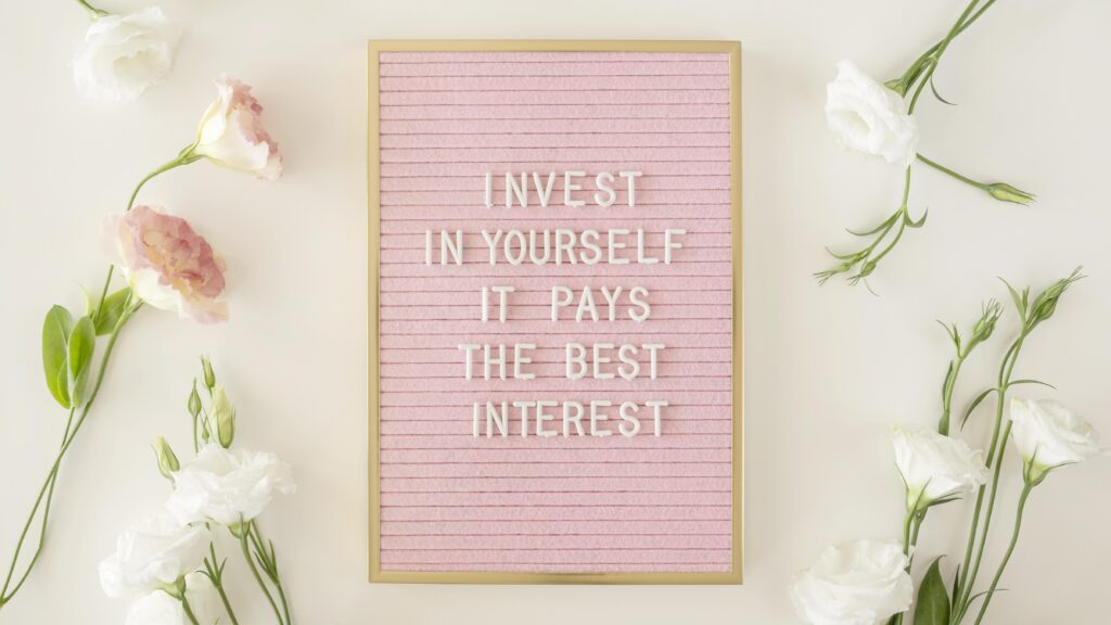 """pink wordboard that reads """"invest in yourself it pay the best interest"""""""